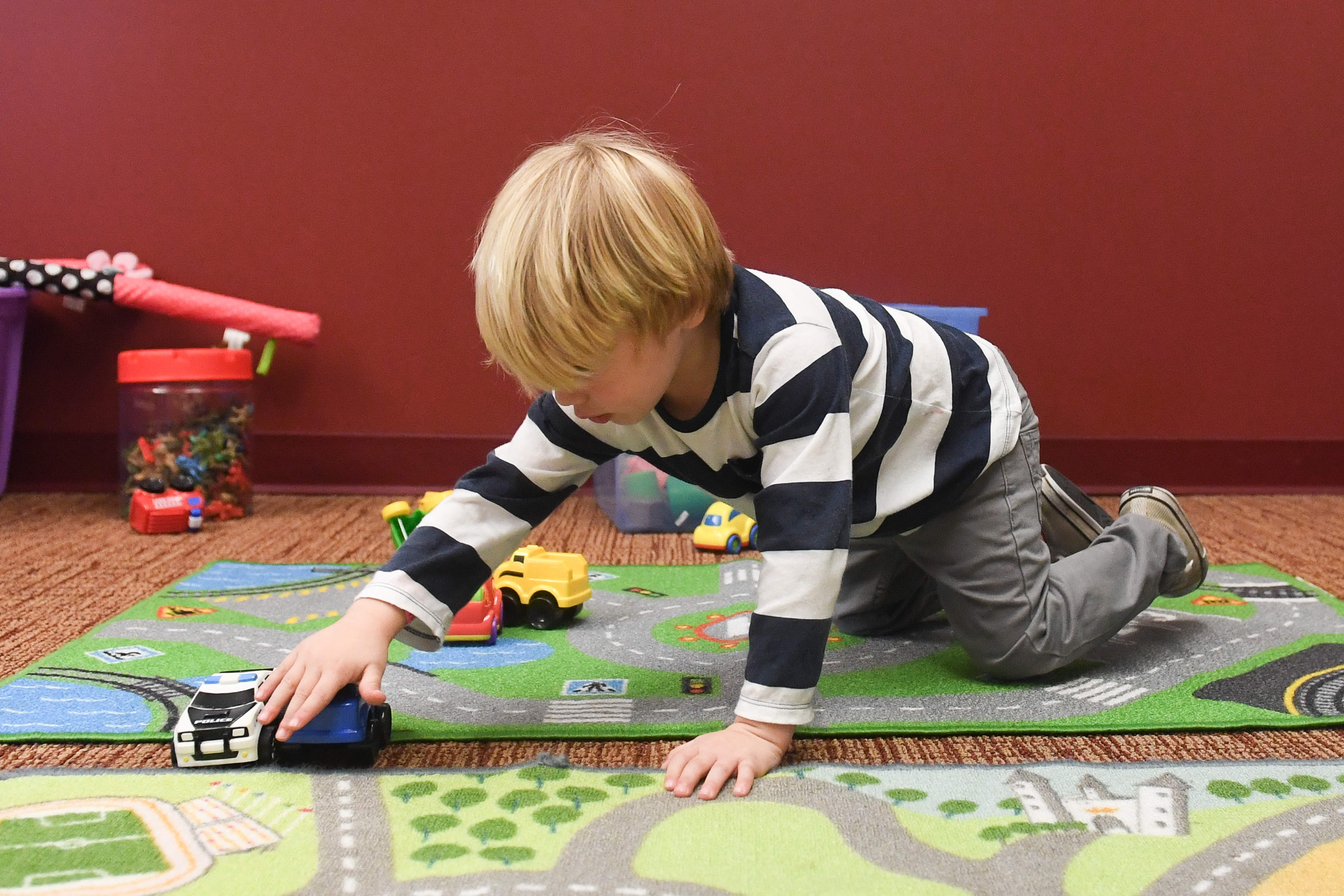 small boy playing with toy cars